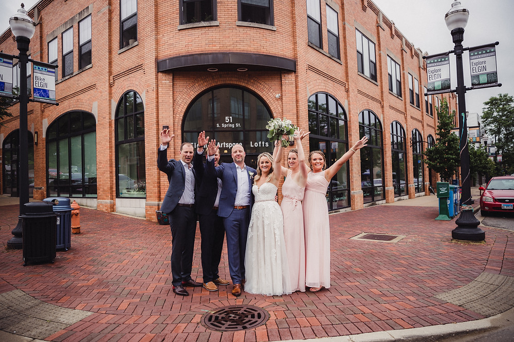 wedding party cheers in front of The Loft of Elements Preserved, Elgin, IL