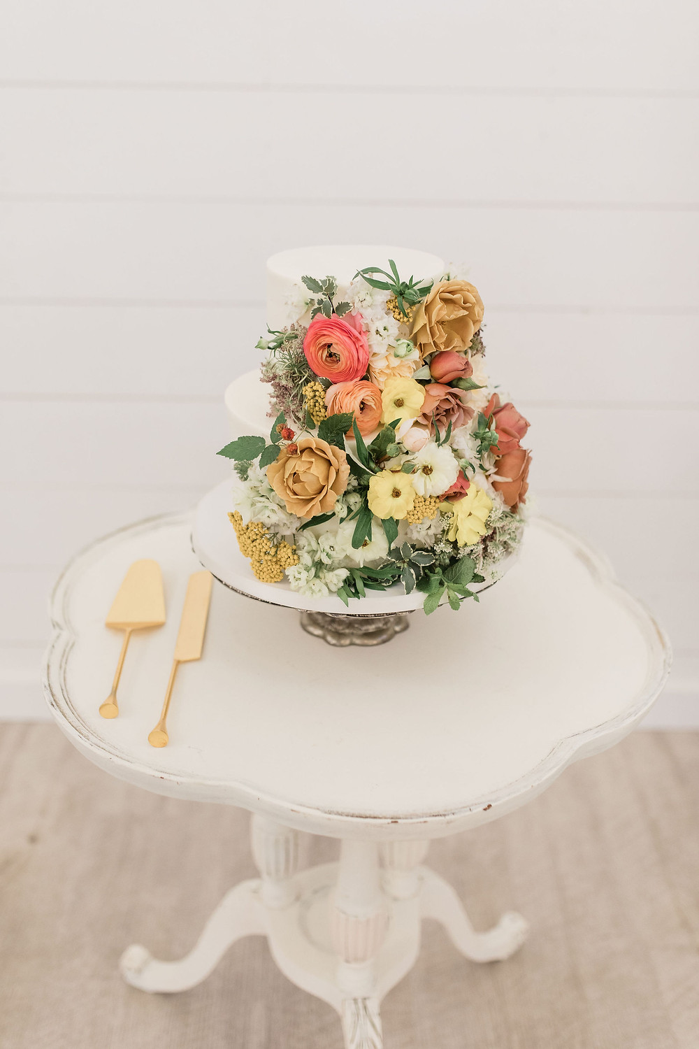 Simple white tables are perfect for the intimate cake; this one styled with all the flowers!