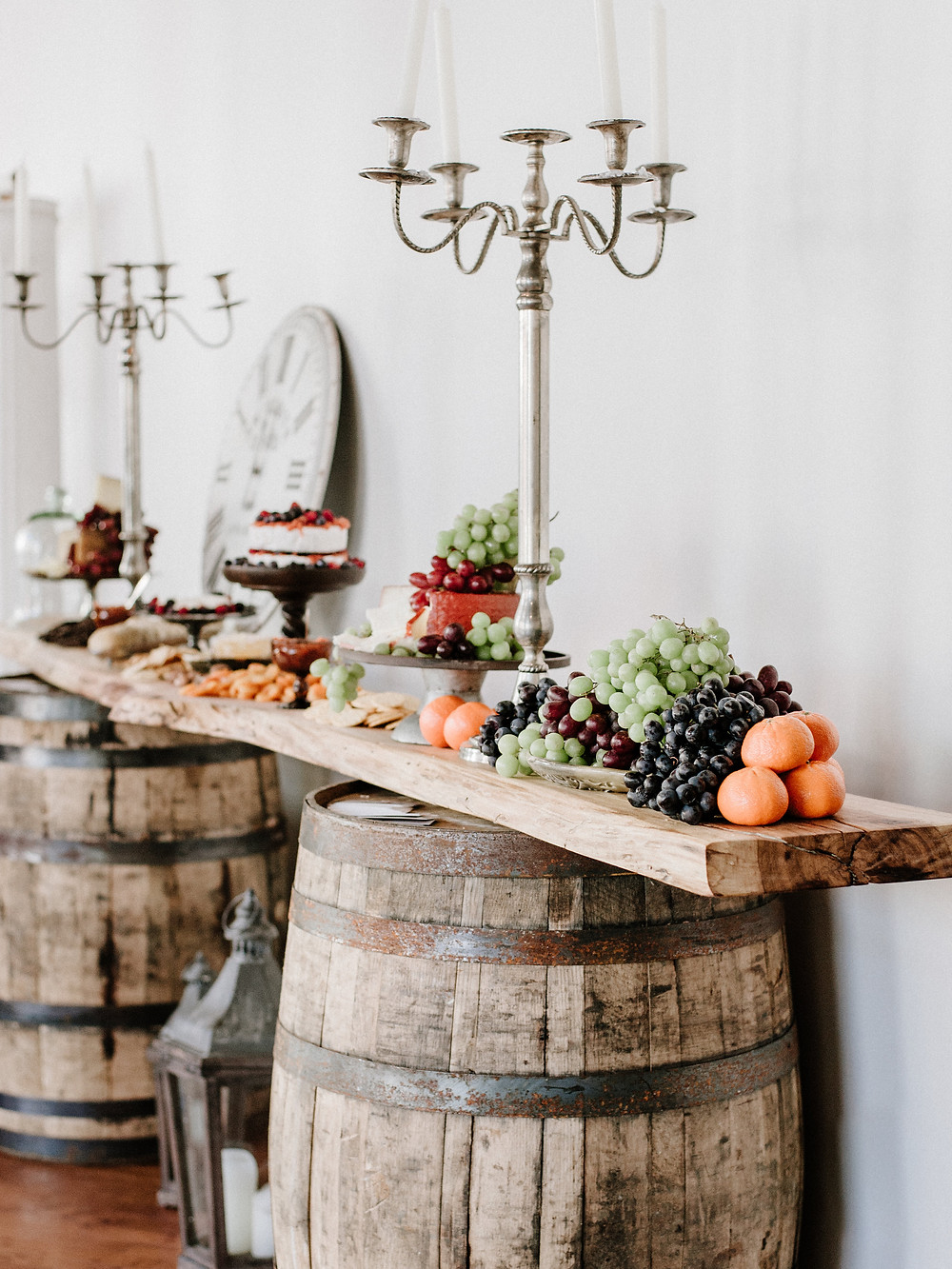 Balanced on two whiskey barrels, a live-edge charcuterie board is filled with delicious appetizers