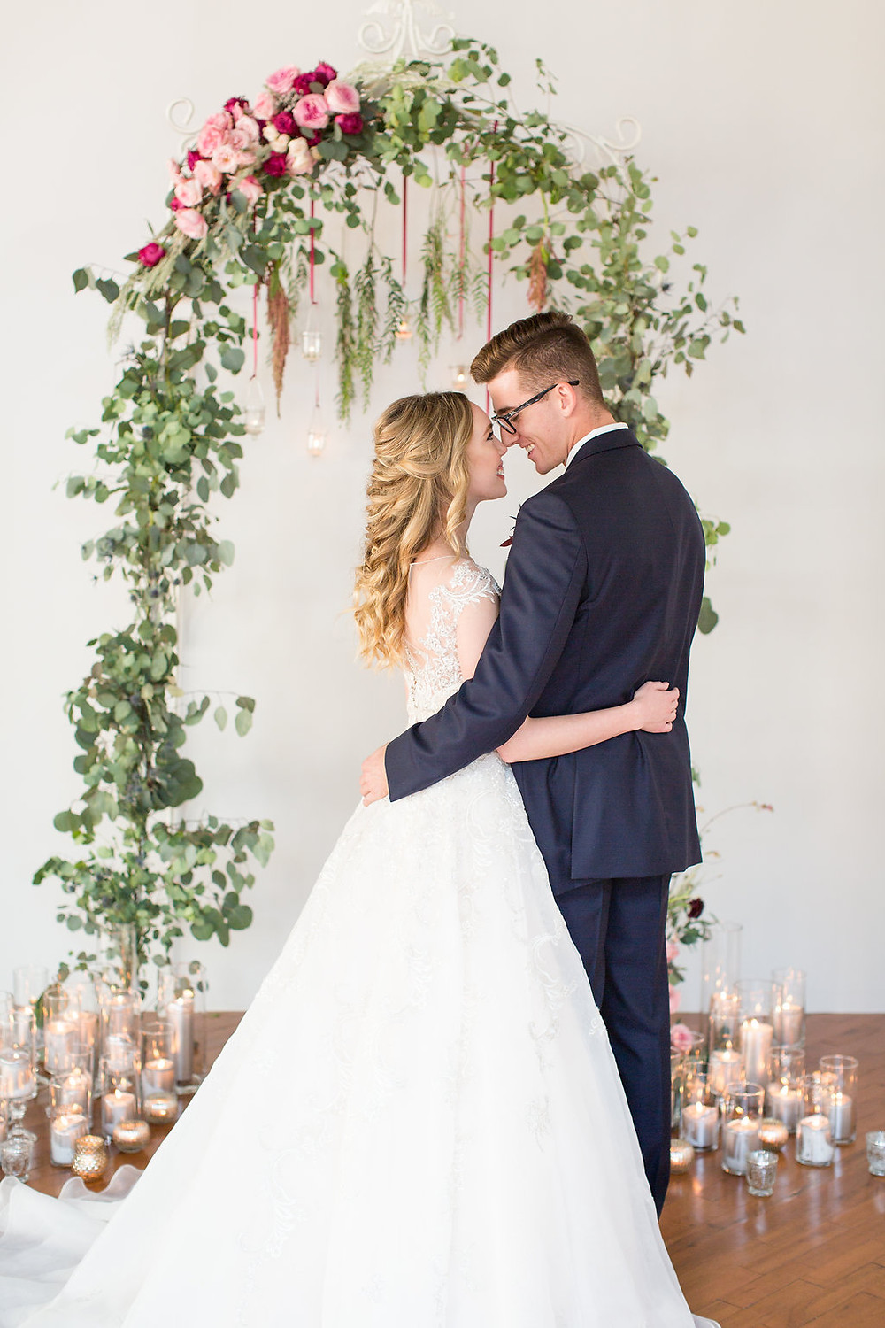 bride and groom posing under white iron arbor filled with florals