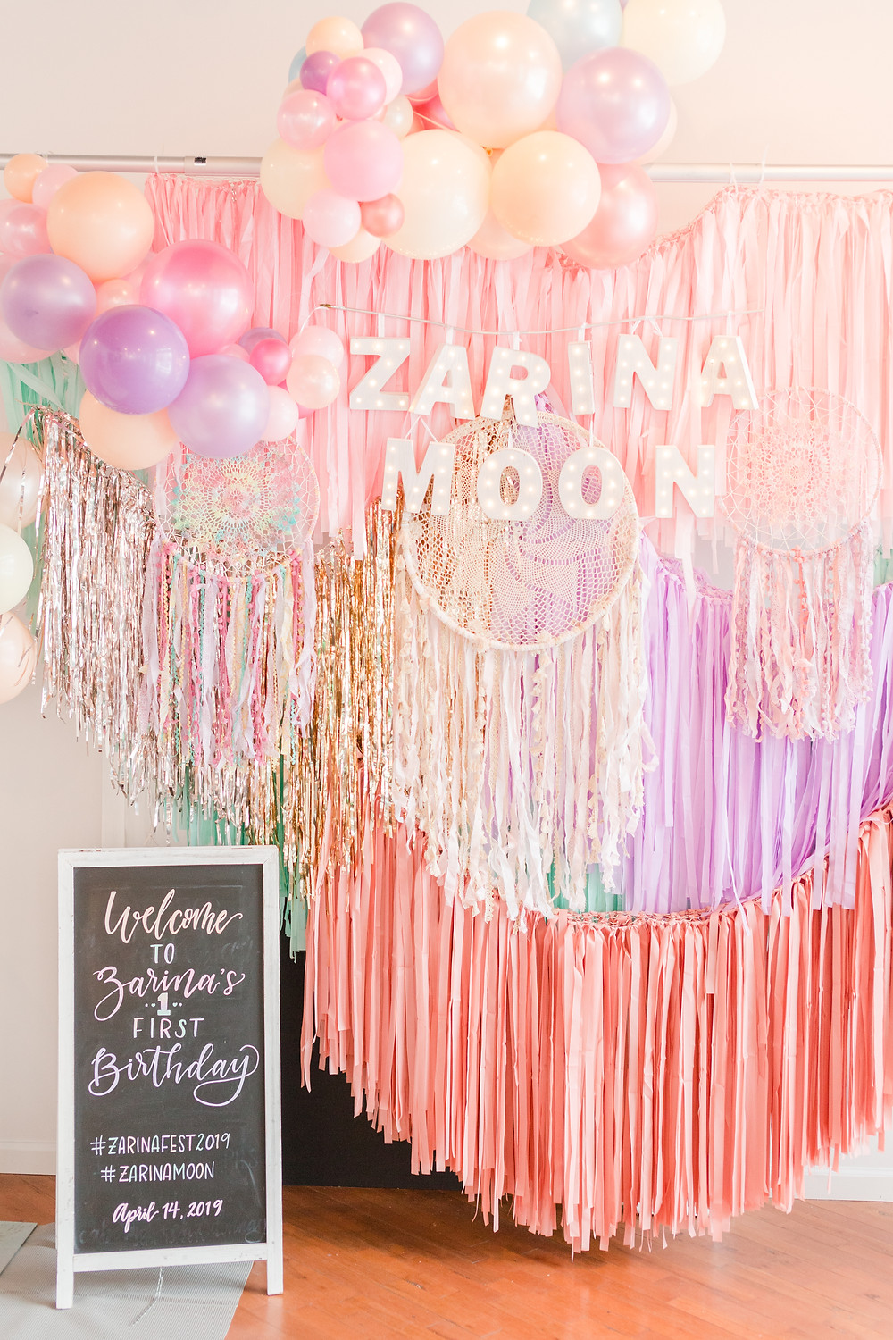 Boho-style backdrop in colorful balloons, streamers, and dream catchers