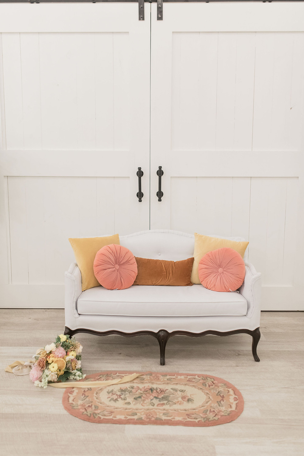 white lounge seating accented with apricot, butterscotch and caramel colored pillows