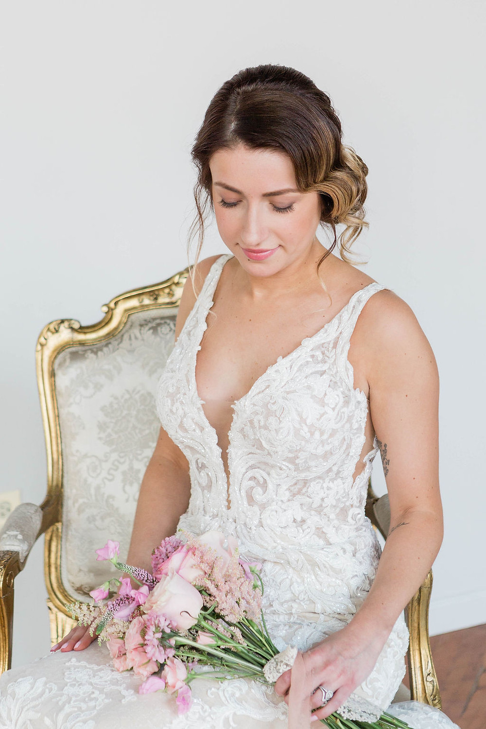 bride seated on vintage chair with floral bouquet