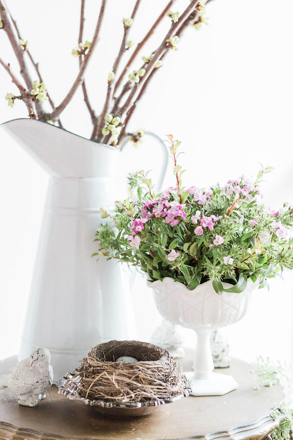 Table display holds birds nest, tiny pink florals, and springtime twigs in a french enamel vintage pitcher