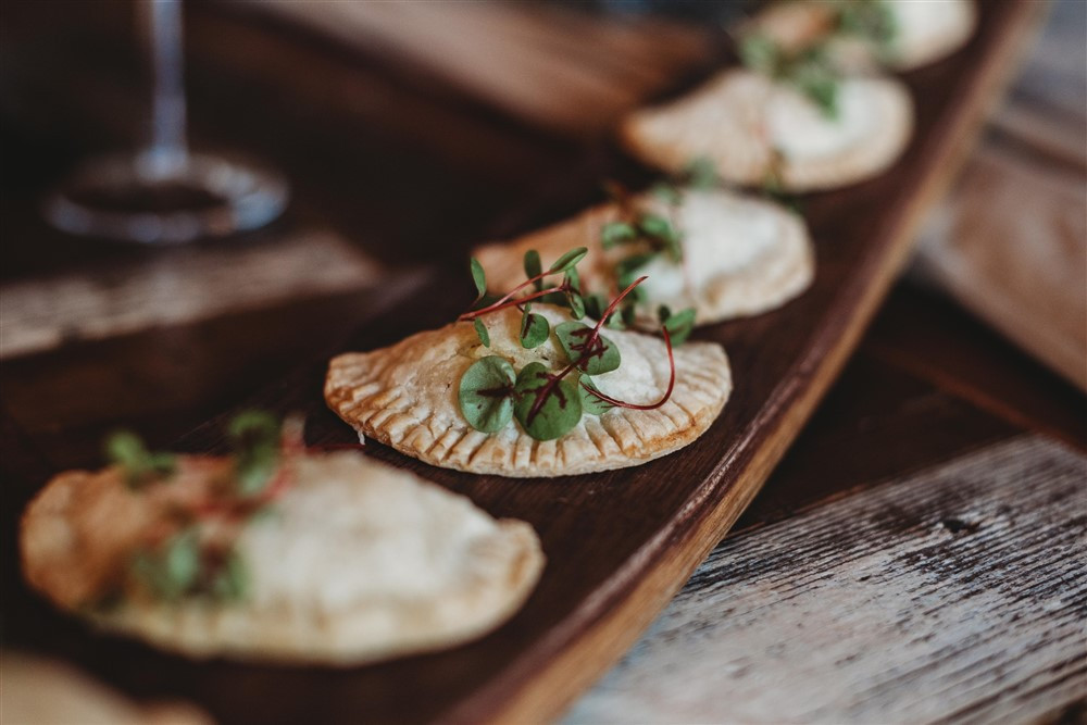 Hand pies served on wooden board with greens as garnish