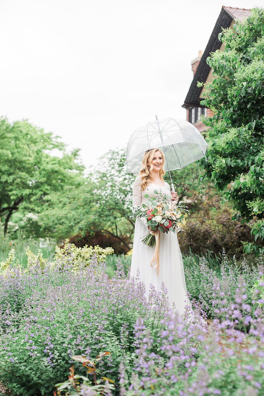 Beautiful bride carries an umbrella as she walks through the mansion gardens