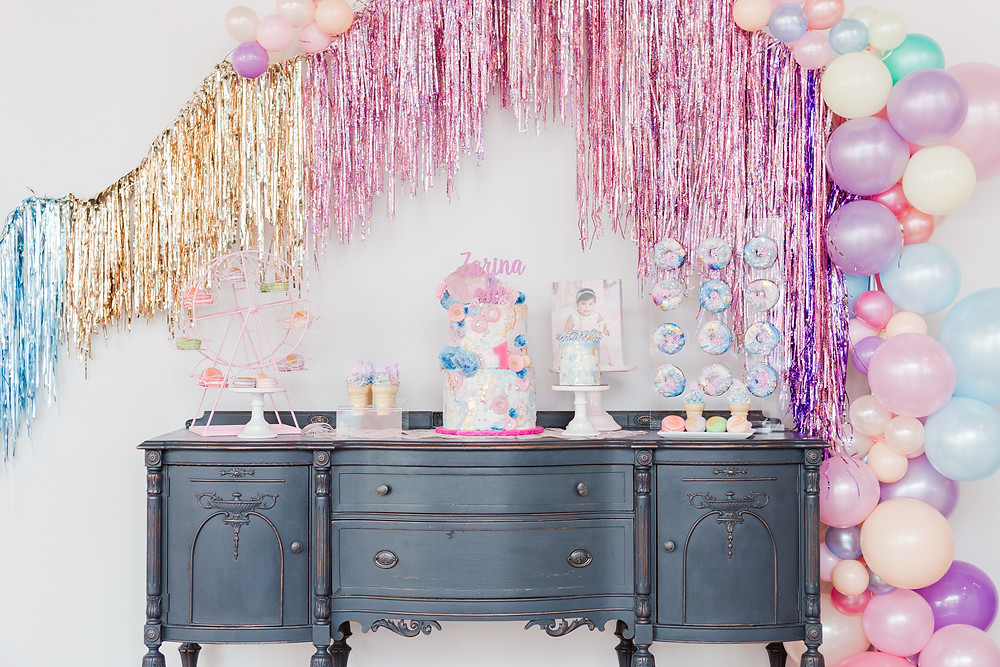 Black buffet serves as sweets table for doughnuts, macarons, layered cake and smash cake