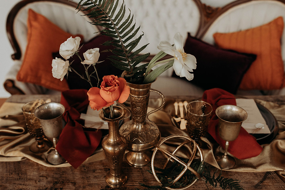 Tablescape of brass geometrics, floral vessels, and gold runner for moody, boho styling.