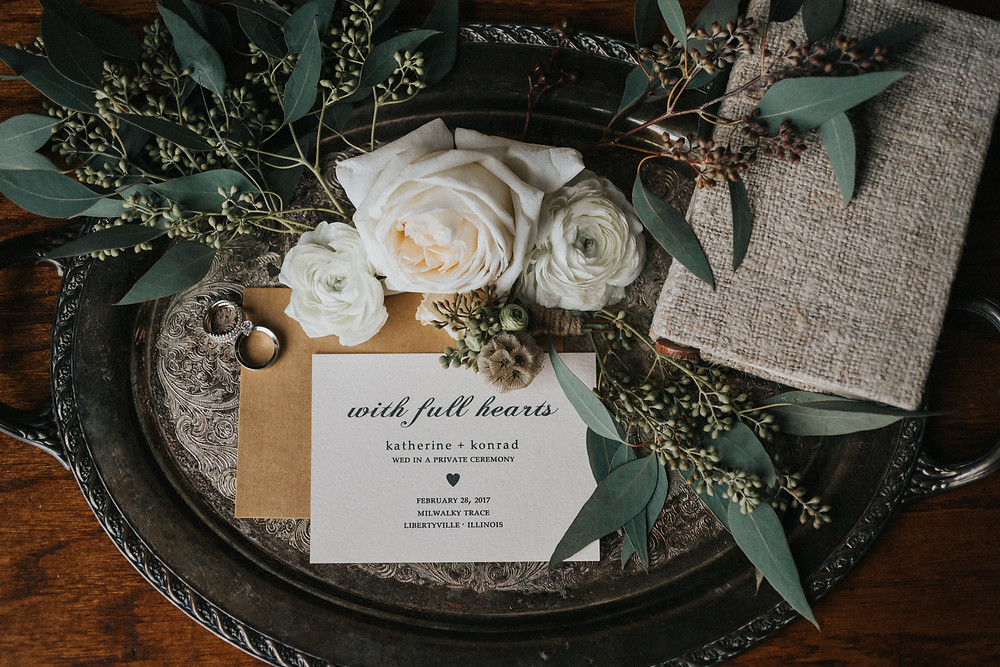 Gather the details for a styled photo of rings, flowers, invitations, and vow book, on a silver tray.