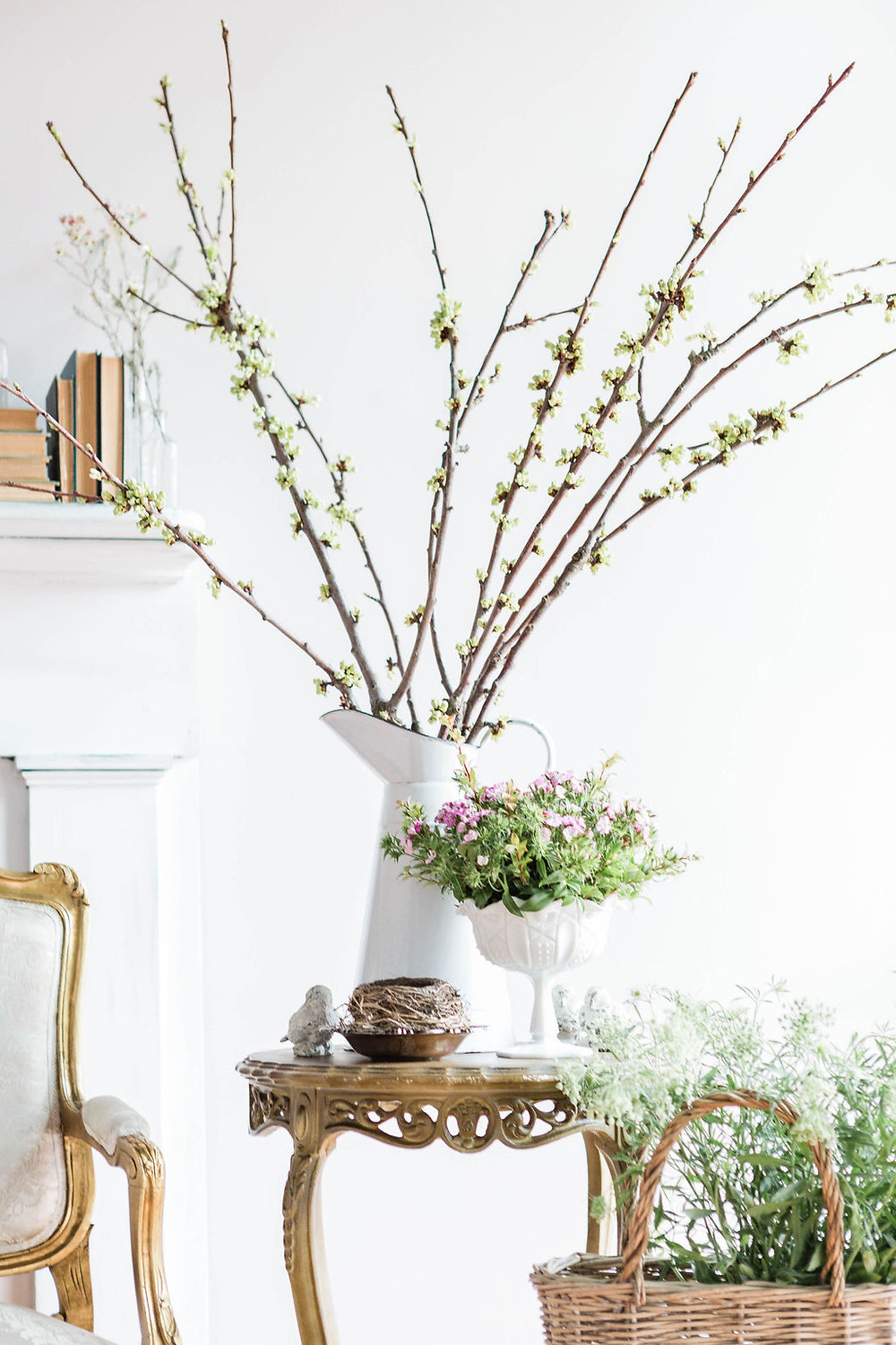 Buds and blossoms signaling springtime, along with a fallen bird nest and stone birds create a simple vignette