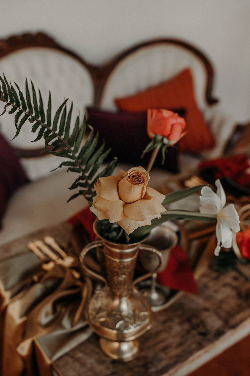 Brass vase holds florals for sweetheart table in moody orange and gold colors