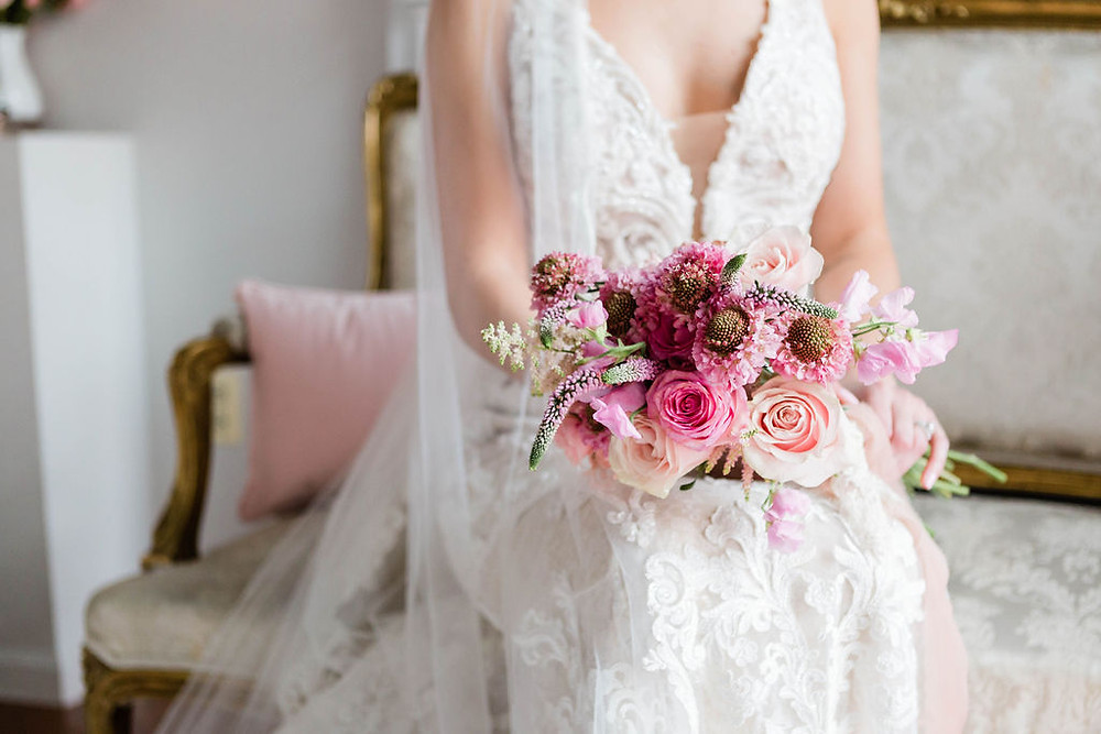 bride holds simple floral bouquet, which is perfect for an elopement wedding ceremony