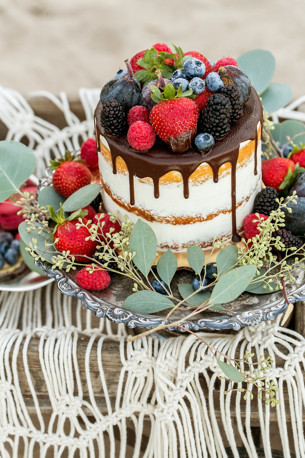 Naked cake dressed with fresh fruit and dripping chocolate for beach picnic celebration