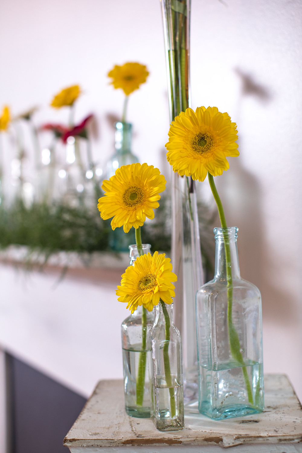 Vintage Mantel designed with vintage bottles holding stems of Gerbera Daisies.