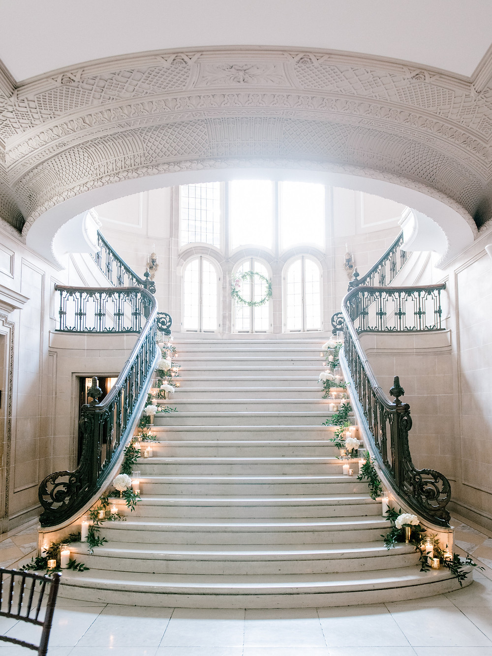 Marble stairwell filled with candles and greenery at the Armour House