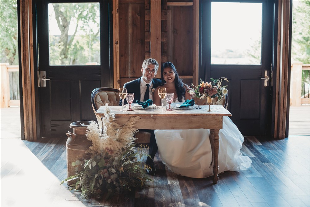 Joy Farm Table and vintage Straw Settee with farm decor for the bride and grooms dining spot