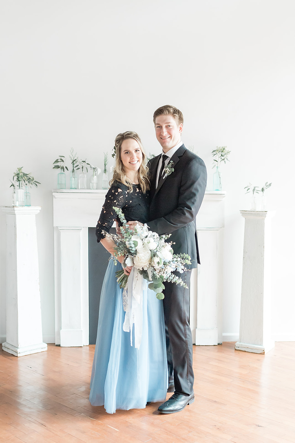 Bride and groom pose in front of vintage mantel accented with blues and greens.  Photo credit: Valerie Michele Photography