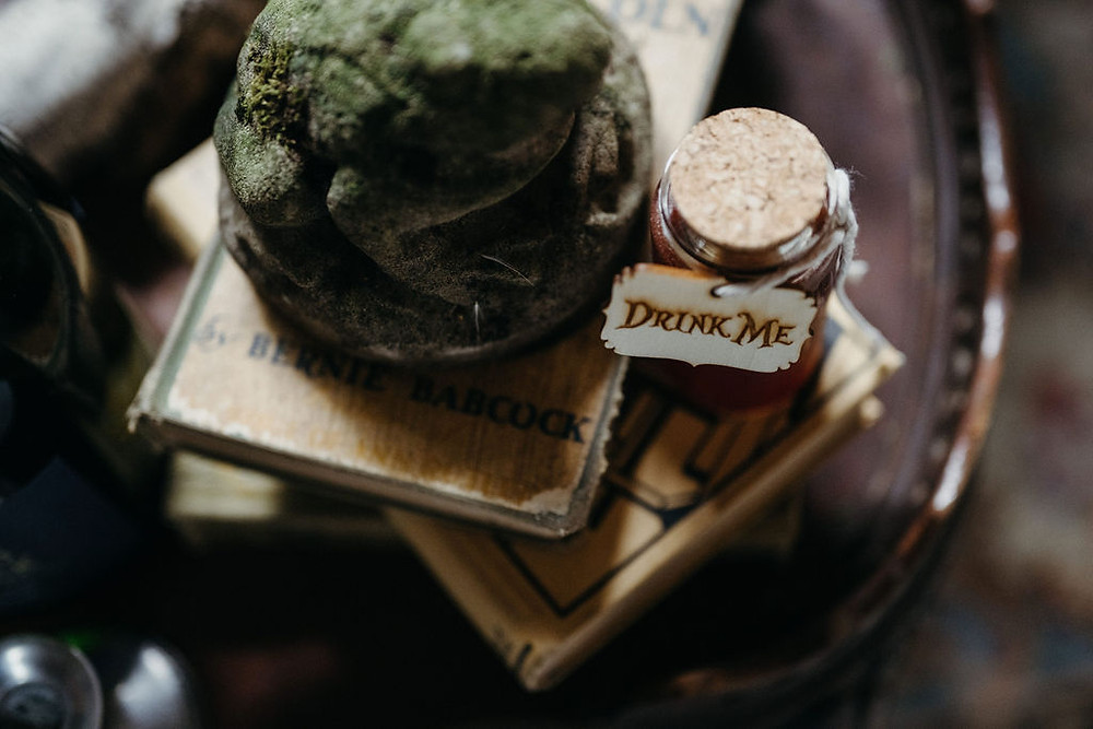 mossy frog sits perched on a stack of vintage books in Alice in Wonderland styled shoot