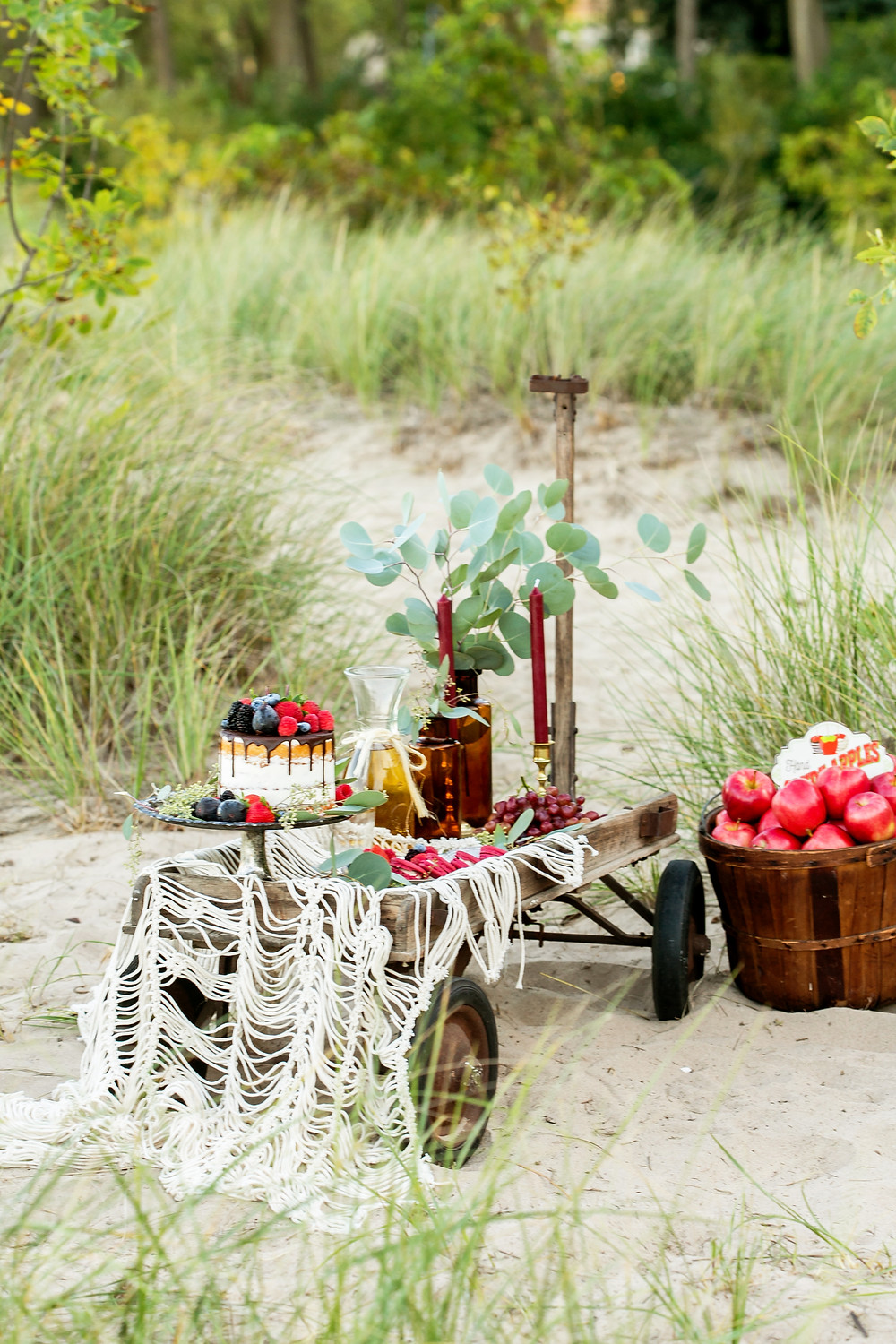 Picnic at the beach with vintage wagon sweets table and apple basket filled with treats