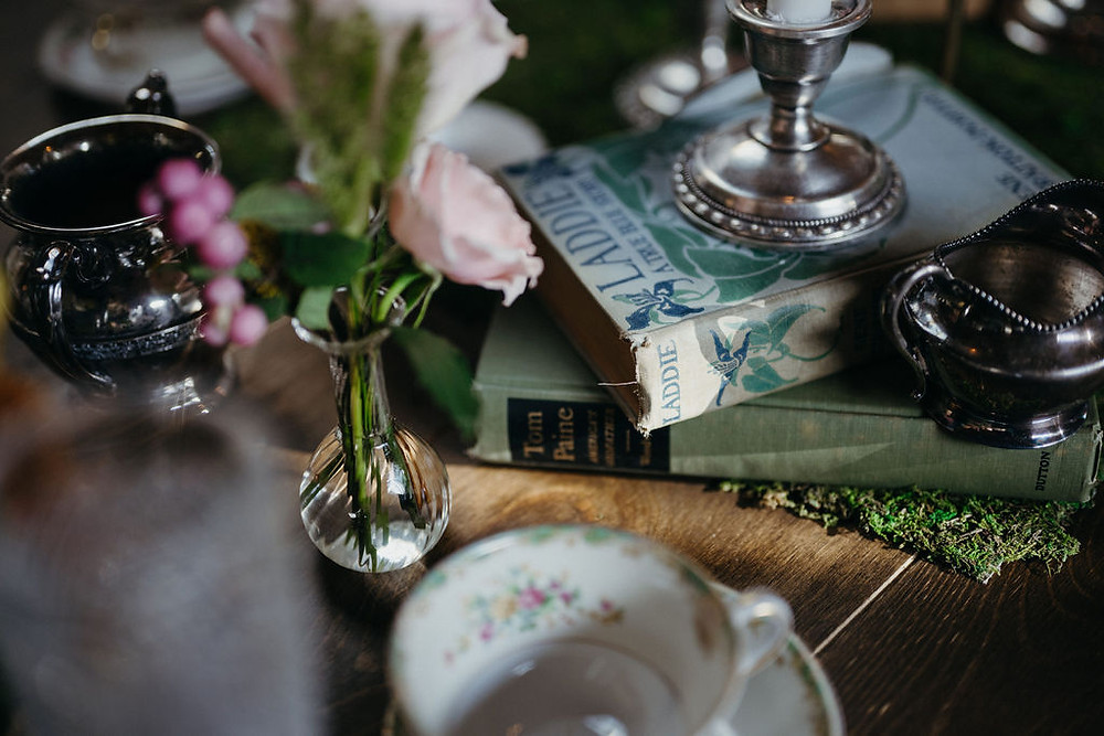vintage books on tablescape with bud vases and vintage china teacups