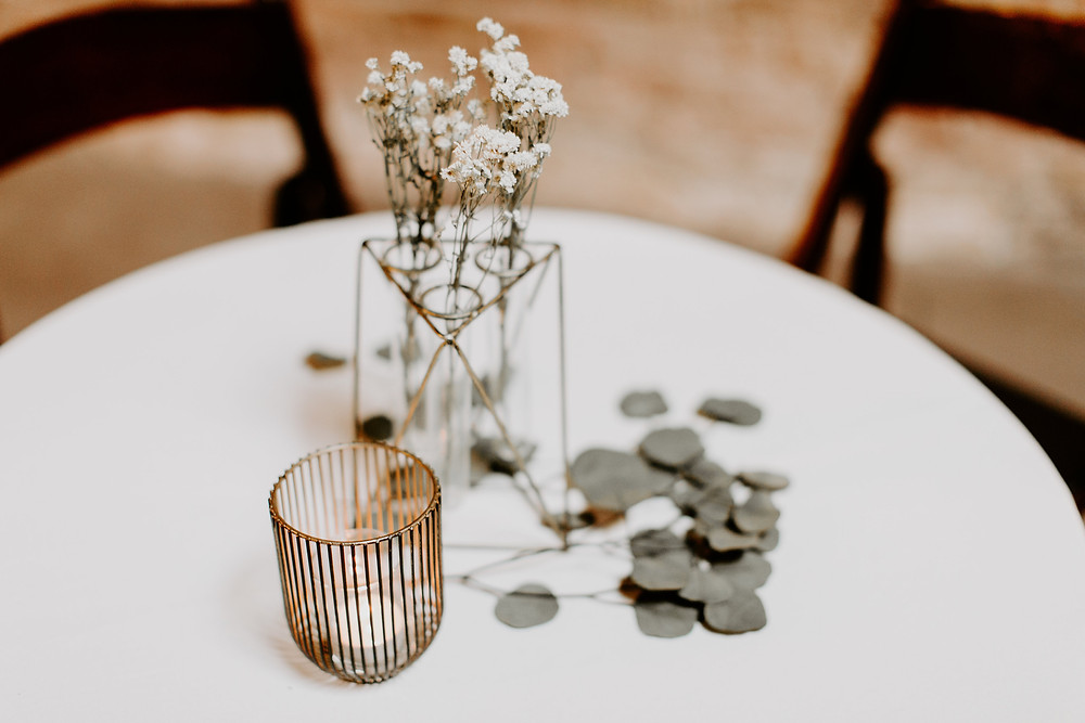 Table decor included mercury glass candles, geometric vector vases, and dried flowers.
