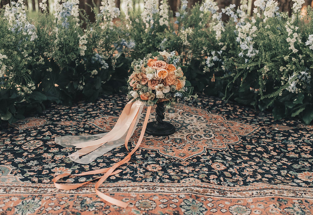 Bridal bouquet perfectly matches the vintage area rug surrounded by beautiful ferns in the ceremony area
