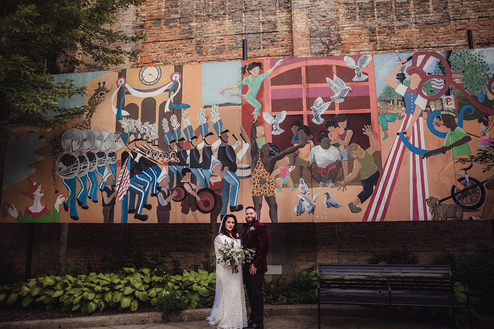 Bride and Groom pose in front of mural painted in urban Elgin, IL.