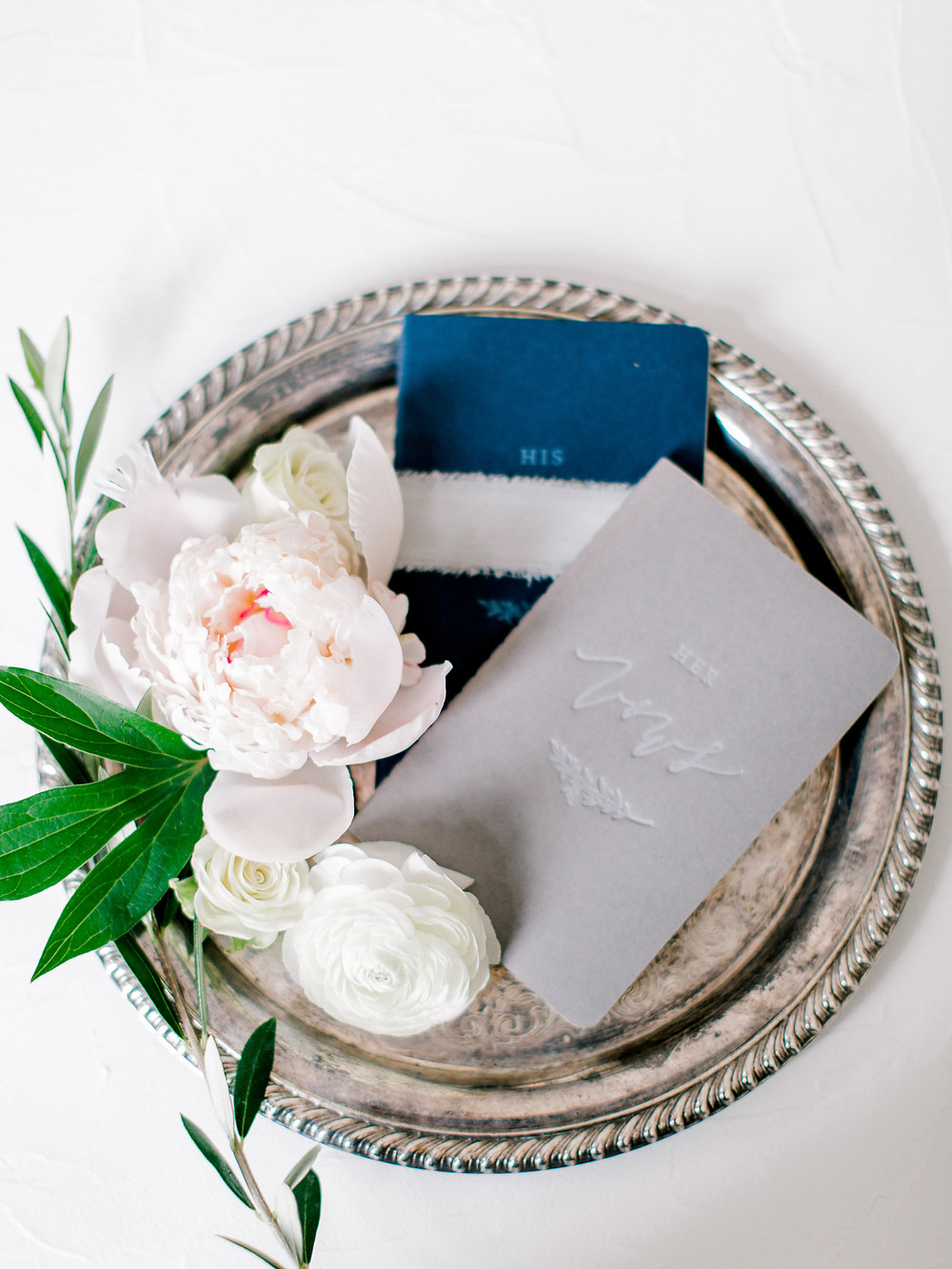 Silver tray displaying all the details; flowers, invitations and more