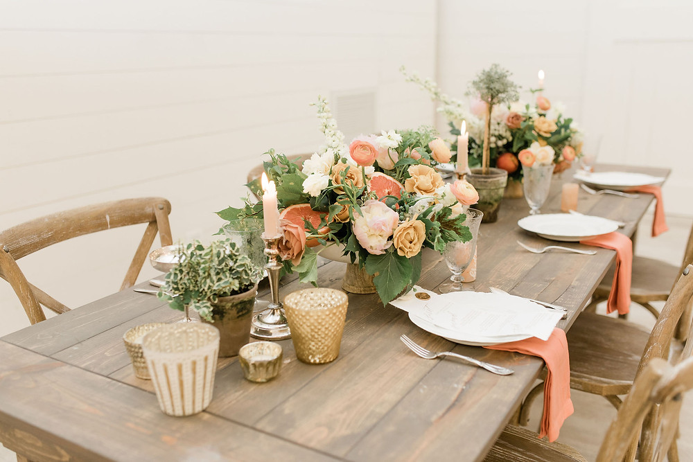 Farm tables set with mercury glass, silver candleholders and blush candles, and dramatic centerpieces accented with real fruit!