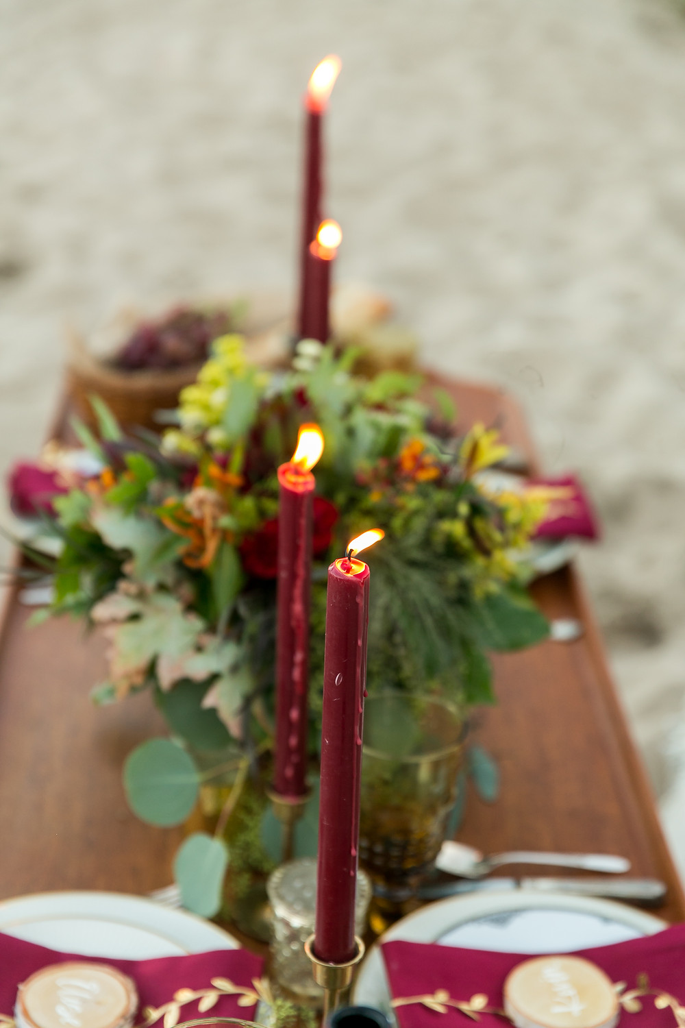 Candles lit on the tiny farm table add charm to beach picnic