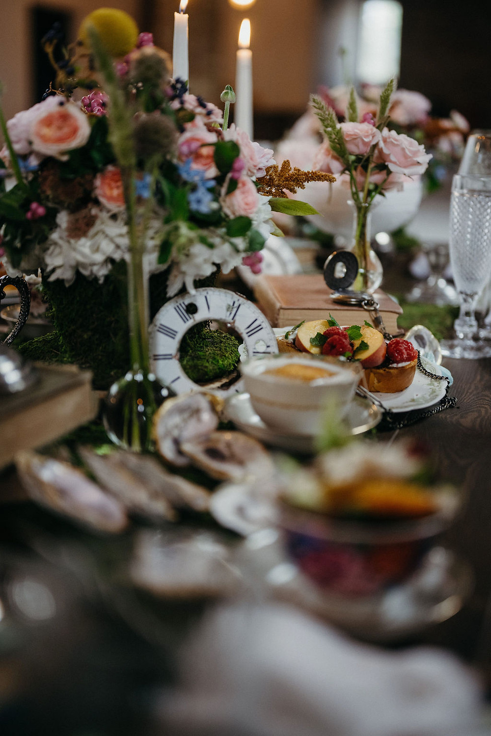 clock face, pocket watch, bud vases, moss, and teacups set the scene for styled tablescape