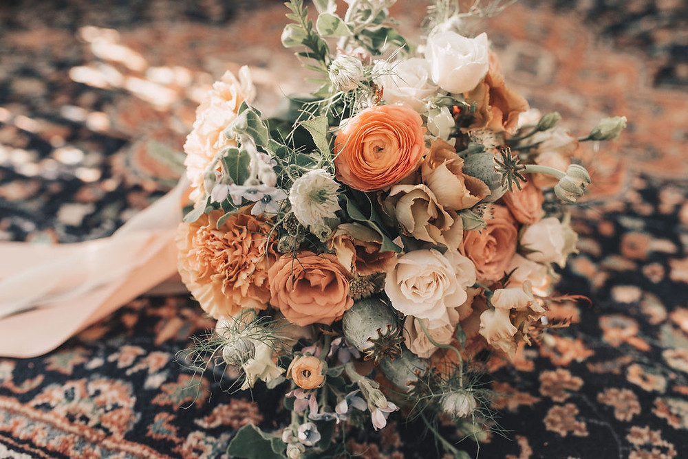 Bridal bouquet placed on top of vintage area rug ties the colors together perfectly