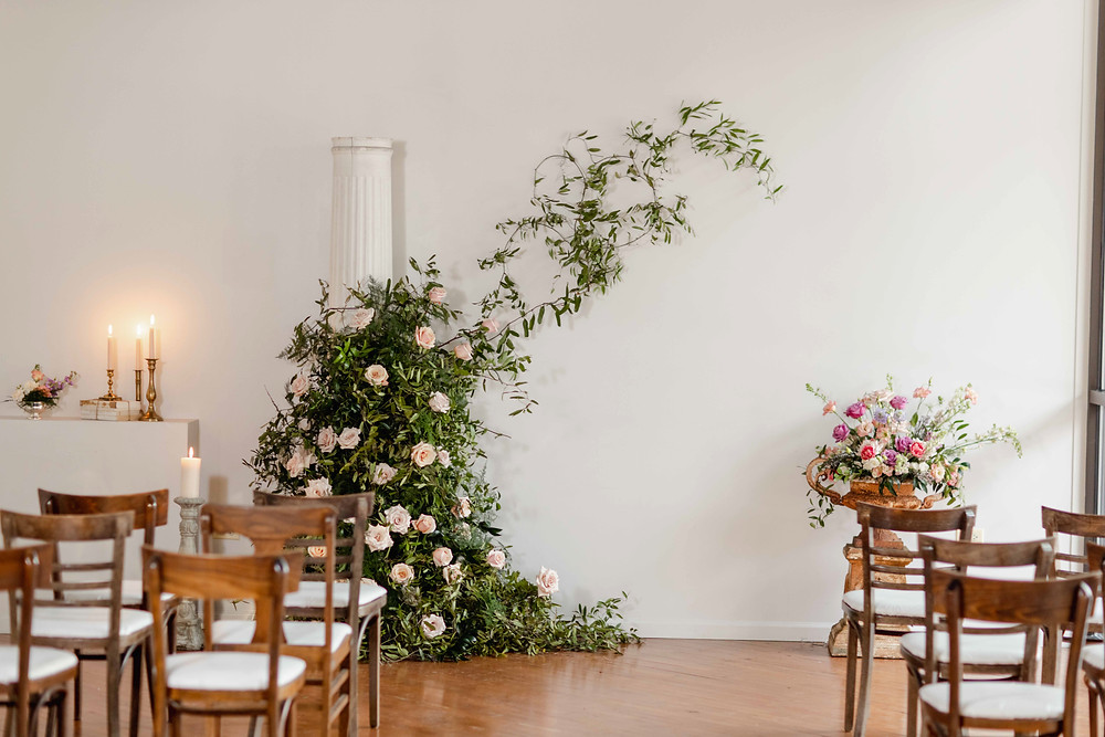 Climbing greenery and roses fill a vintage urn for unique ceremony backdrop