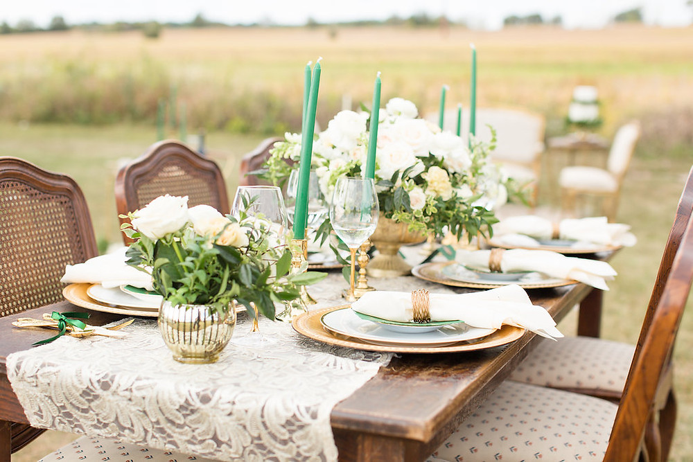 Harvest Table set for guests accented with emerald green and gold table settings.
