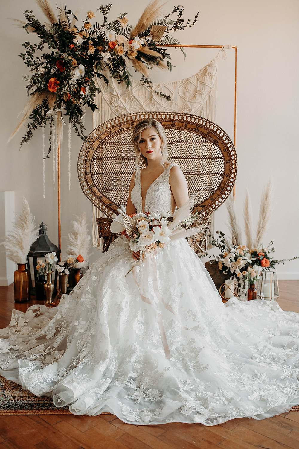 Bride posed on peacock chair in front of macrame hanging on copper arbor