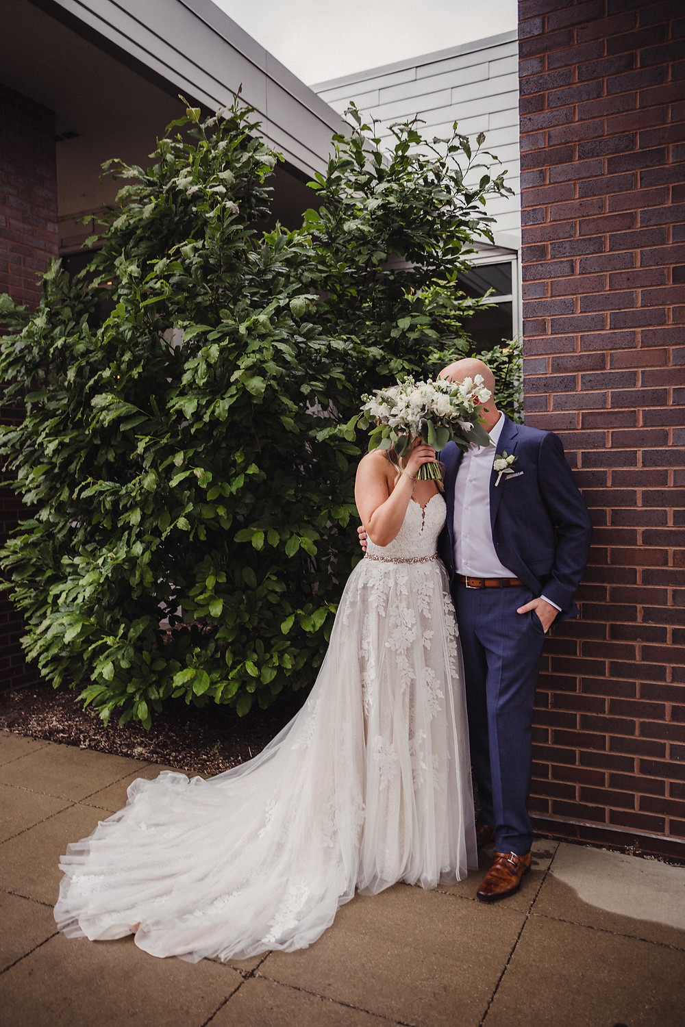 bride and groom share a secret kiss outside The Loft of Elements Preserved in Elgin, IL