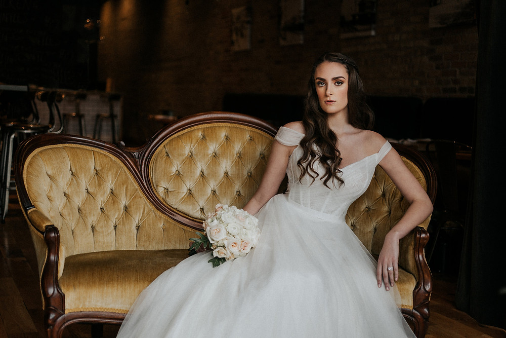 Bride poses on vintage gold settee with floral bouquet