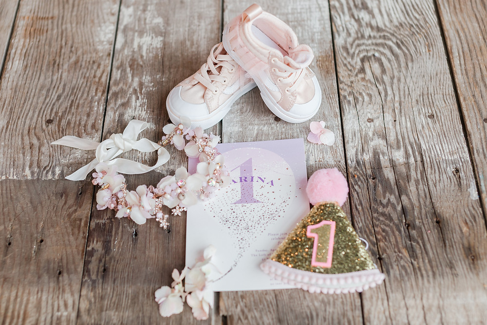 Invitation, shoes, flower crown details on farm table for 1st Birthday photos
