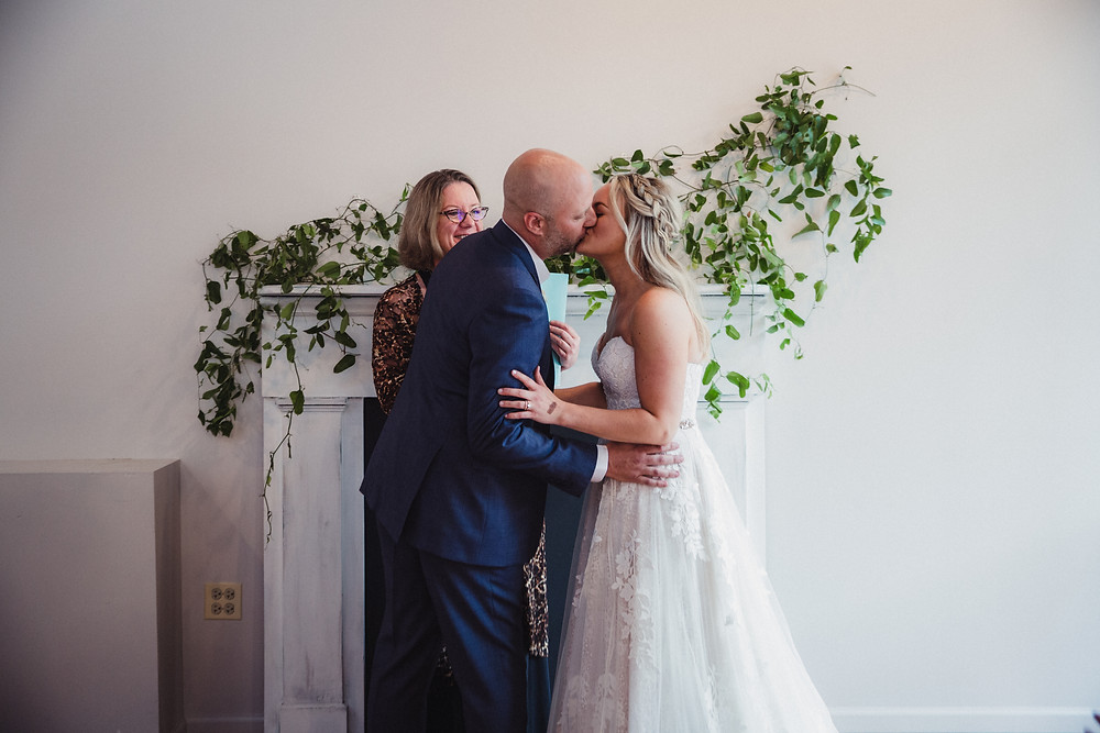 Celebratory first kiss in front of our vintage white mantel at The Loft of Elements Preserved, Elgin, IL