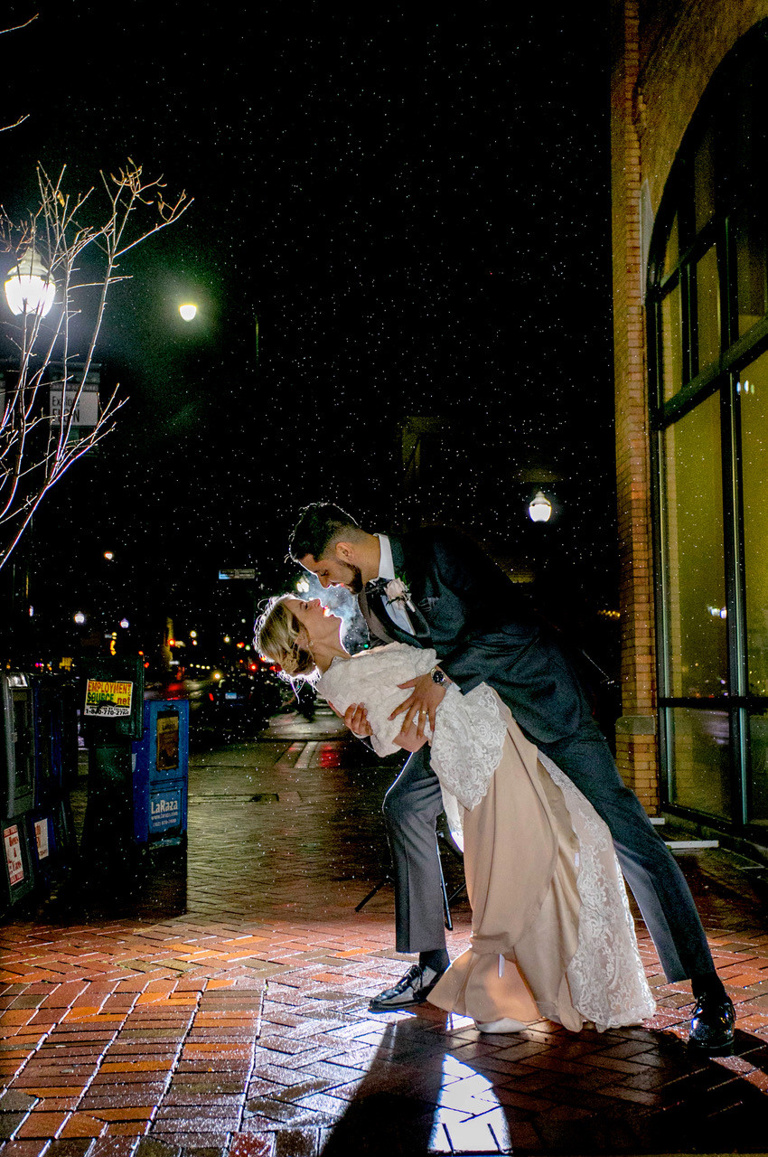 Couple share a kiss outside their reception venue in Elgin, IL after tiny wedding
