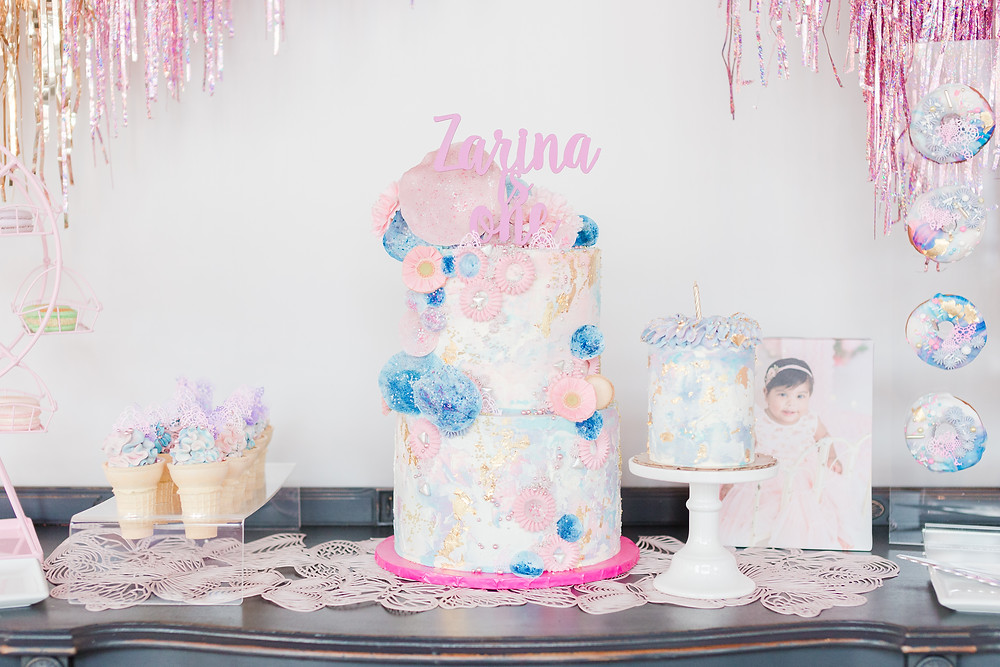 Baby's smash cake and two-tiered cake to serve guests filled with frosting flowers hand-applied