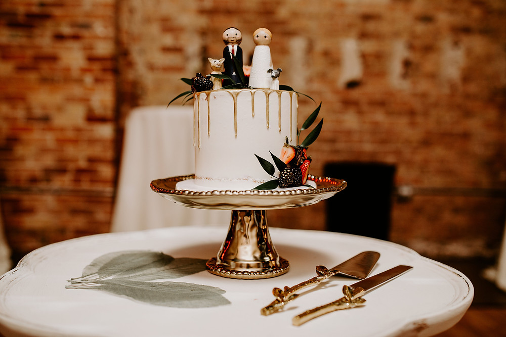 gold cake plate holds wedding cake decorated with couple and puppies