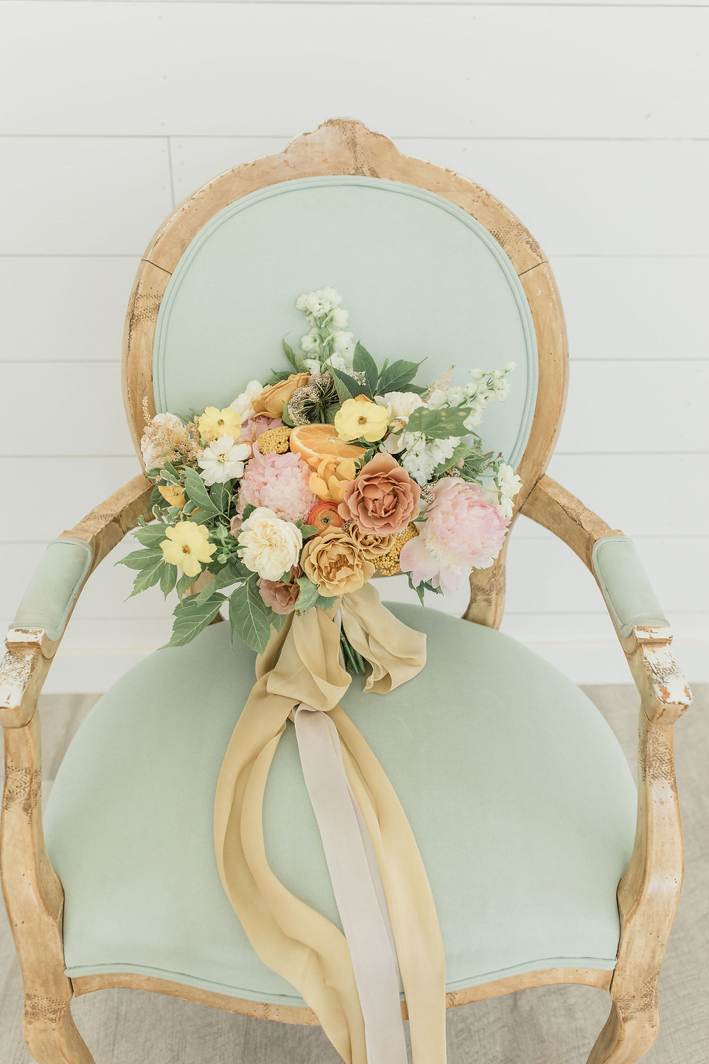 Blush and yellows make up the bridal bouquet placed on our sage green chair