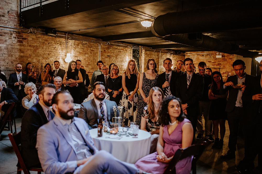 Guests gather to watch prior elopement wedding on monitors, while at wedding reception, Row 24 Events.