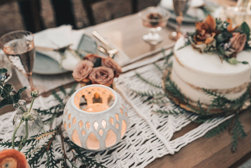 naked cake displayed on sweetheart table with pottery luminaries, macrame and table settings