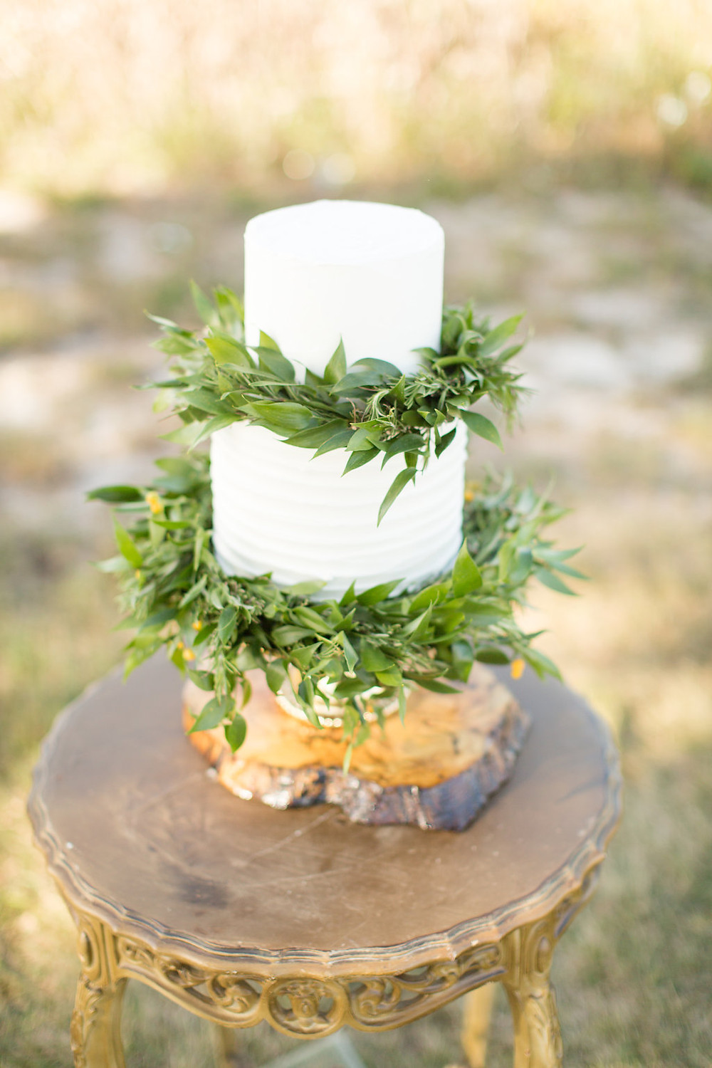 white wedding cake on gold florentine nesting tables for petite wedding ceremony in the fields