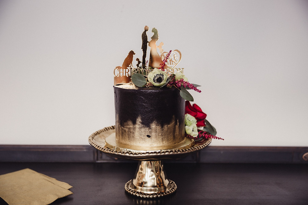 Gold and black wedding cake displayed on gold cake stand