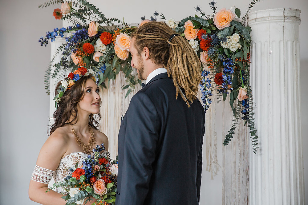 The bride and groom stand in front of vintage column and floral/macrame backdrop for their ceremony at The Loft of Elements Preserved