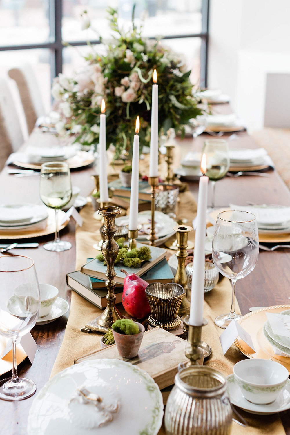The 14 ft. Harvest table was filled with vintage china, brass candlesticks, vintage books, fruit, nuts, and organic material to carry through the woodland-inspired theme.