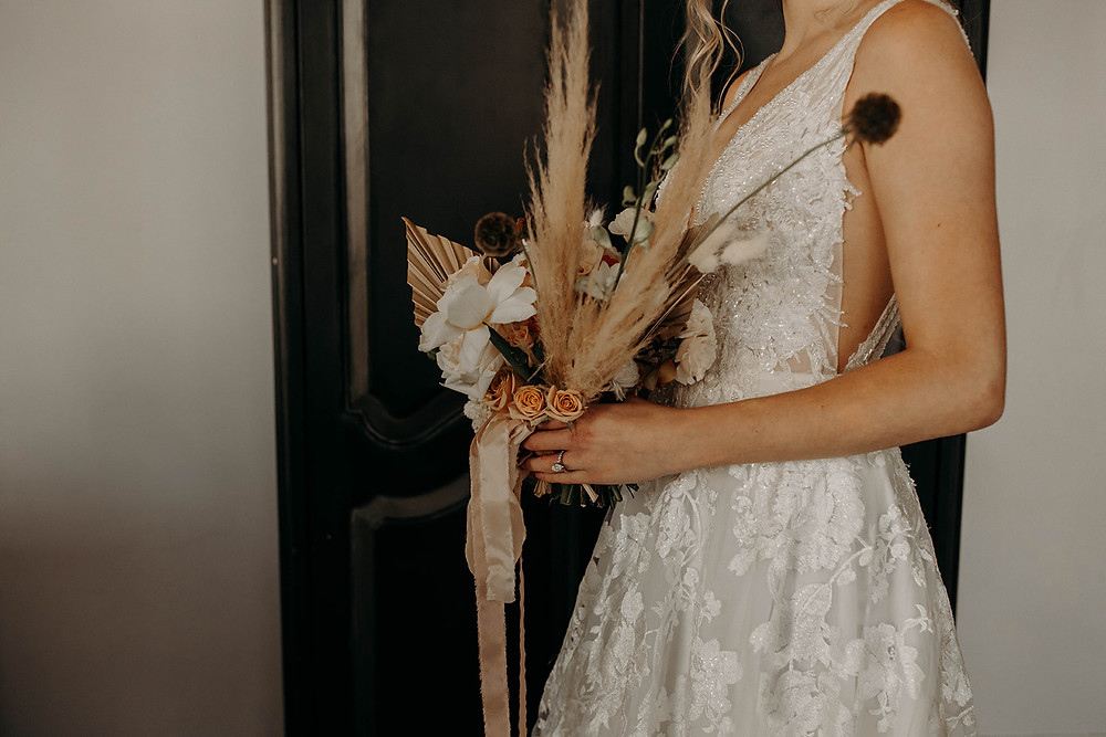 Bride holds simple floral bouquet while showing wedding dress details of lace and sequins.